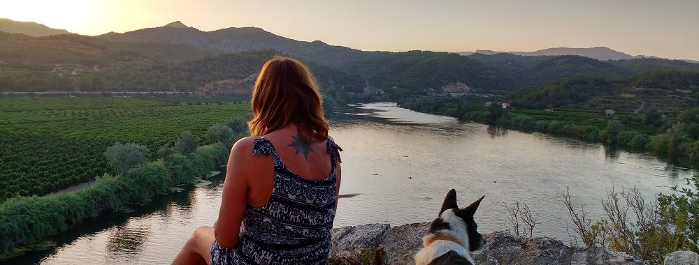 Jane Clements and dog looking out over a river at sunset