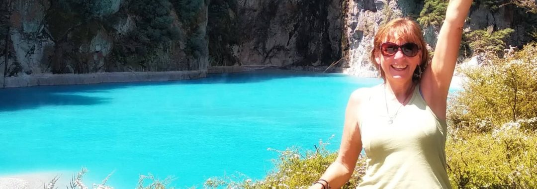 Jane Clements Life Coach in front of a bright blue volcanic lake