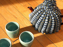 teapot on a table with a woollen teacosy
